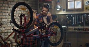 Dois meninos que reparam uma bicicleta em uma garagem filme