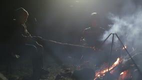 Dois meninos que sentam-se na noite ao lado da fogueira, corrigindo o carvão e a fala filme