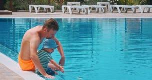 Dois meninos que sentam-se perto da piscina video estoque