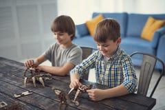 Dois meninos que sorriem ao fazer modelos do mecânico do construtor de madeira imagem de stock