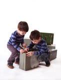 Dois meninos que tentam abrir a caixa de madeira em um fundo branco Imagens de Stock Royalty Free
