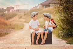 Dois meninos, sentando-se em uma mala de viagem velha grande do vintage, jogando com a Fotos de Stock