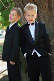 Dois meninos vestidos no smoking que está a árvore próxima Imagem de Stock