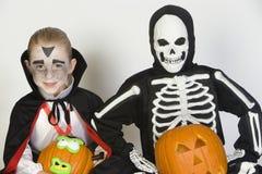 Dois meninos vestidos nos trajes de Dia das Bruxas que guardam Jack-O-lanternas Imagem de Stock Royalty Free