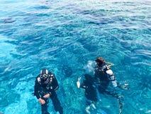 Dois mergulhadores em ternos pretos do mergulho autônomo, em um homem e em uma mulher com garrafas de oxigênio afundam-se sob a á Fotos de Stock