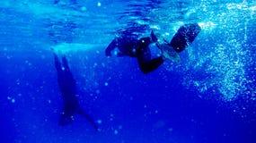 Dois mergulhadores na obscuridade - água azul e bolhas de ar imagens de stock royalty free
