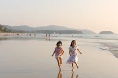 Dois miúdos asiáticos que funcionam na praia Fotografia de Stock