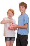 Dois miúdos com banco piggy foto de stock royalty free