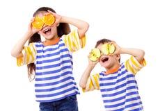 Dois miúdos engraçados com frutos nos olhos Imagem de Stock