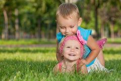 Dois miúdos felizes na grama Foto de Stock Royalty Free