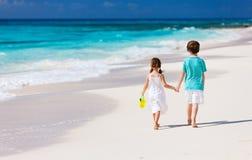Dois miúdos que andam ao longo de uma praia nas Caraíbas Fotos de Stock Royalty Free