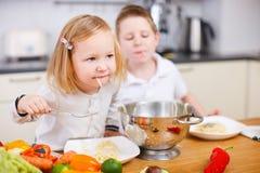 Dois miúdos que comem o espaguete Foto de Stock