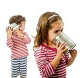 Dois miúdos que falam em um telefone do estanho imagens de stock royalty free