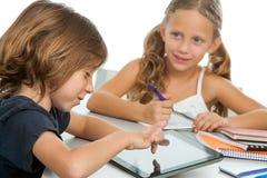 Dois miúdos que fazem trabalhos de casa na tabuleta digital. fotos de stock royalty free