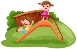 Dois miúdos que jogam na corrediça Imagens de Stock Royalty Free