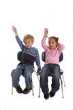Dois miúdos que levantam suas mãos na escola Fotografia de Stock
