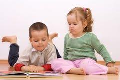 Dois miúdos que olham o livro do conto Imagens de Stock