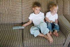 Dois miúdos que prestam atenção à tevê Fotografia de Stock Royalty Free