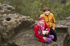 Dois miúdos que sentam-se em uma rocha Imagens de Stock Royalty Free