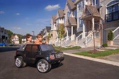 Dois miúdos que têm o divertimento no carro do brinquedo imagens de stock royalty free