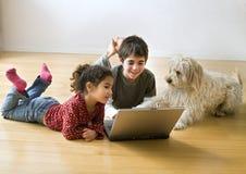 Dois miúdos com computador portátil e um cão Imagens de Stock Royalty Free