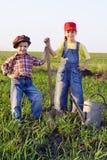 Dois miúdos com pá e podem Fotografia de Stock Royalty Free