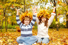 Dois miúdos em grinaldas principais outonais Fotografia de Stock Royalty Free