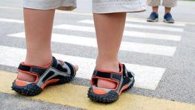 Dois miúdos que cruzam um cruzamento de pedestre alinhado Fotos de Stock