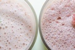 Dois milks shake com banana e morango imagens de stock royalty free