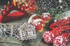 Dois mitenes e doce de fruta da massa de torta, com uma casa de pão-de-espécie na tabela do Natal Copie o espaço toned neve Imagens de Stock Royalty Free