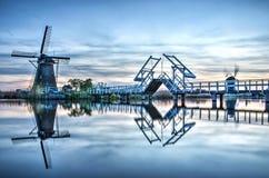 Dois moinhos de vento e pontes levadiças que refletem durante a hora azul fotos de stock royalty free