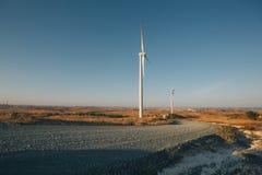 Dois moinhos de vento pela borda da estrada em uma paisagem rural em Chipre fotografia de stock