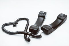 Dois monofones com os fios tecidos em um heart-shaped Fotos de Stock