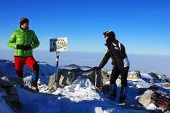 Dois montanhistas novos que comemoram sobre o pico de Peleaga, Romênia Imagens de Stock