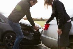 Dois motoristas que discutem sobre dano aos carros após o acidente Fotografia de Stock Royalty Free