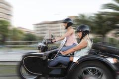 Dois mulheres louras da irmã feliz no side-car bike o sorriso e felizes imagens de stock