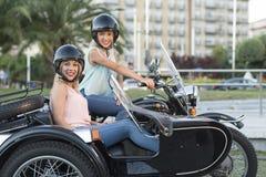 Dois mulheres louras da irmã feliz no side-car bike o sorriso e felizes imagens de stock royalty free