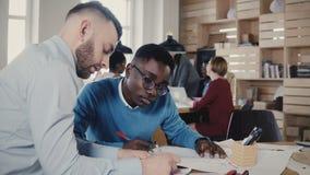 Dois multi colegas étnicos trabalham no projeto da arquitetura no espaço de escritórios na moda do sótão, trabalhos de equipa no  filme