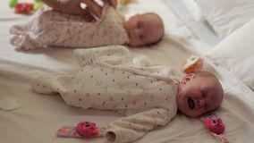 Dois neonatos estão encontrando-se em suas partes traseiras, um delas estão fazendo a ginástica para seus pés Saúde do ` s das cr vídeos de arquivo