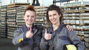Dois operários fêmeas felizes que abraçam mostrando os polegares acima no armazenamento filme