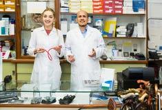 Dois ortopedistas que trabalham na loja especial com bens ortopédicos Imagem de Stock Royalty Free