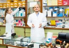 Dois ortopedistas que trabalham na loja especial com bens ortopédicos Fotografia de Stock Royalty Free