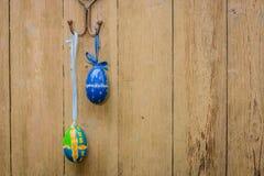 Dois ovos da páscoa na porta de madeira de Brown imagem de stock