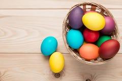 Dois ovos da páscoa perto de uma cesta de vime dos ovos no de madeira Imagem de Stock Royalty Free