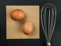 Dois ovos de Brown crus e um batedor de ovos do utensílio da cozinha do metal Foto de Stock Royalty Free