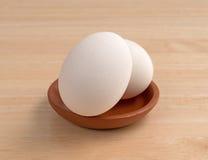 Dois ovos em uma bacia pequena sobre uma tabela de madeira Imagem de Stock