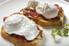 Dois ovos escalfados com bacon no café da manhã cozinhado brinde imagens de stock royalty free