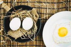 Dois ovos inteiros em uma frigideira do ferro fundido em uma tabela de madeira Foto de Stock Royalty Free