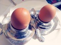 Dois ovos nos copos de ovo de prata para o breaktfast Fotos de Stock Royalty Free