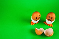 Dois ovos nos suportes com caras em um backround verde Imagem de Stock